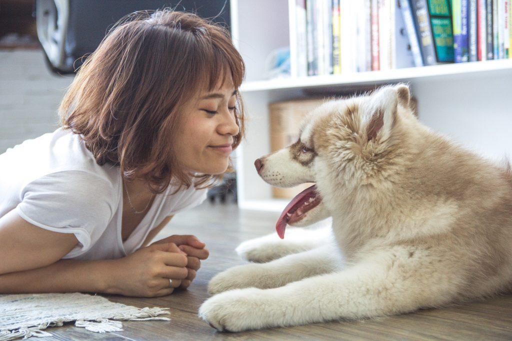 Mädchen mit Hund am Boden im Wohnzimmer