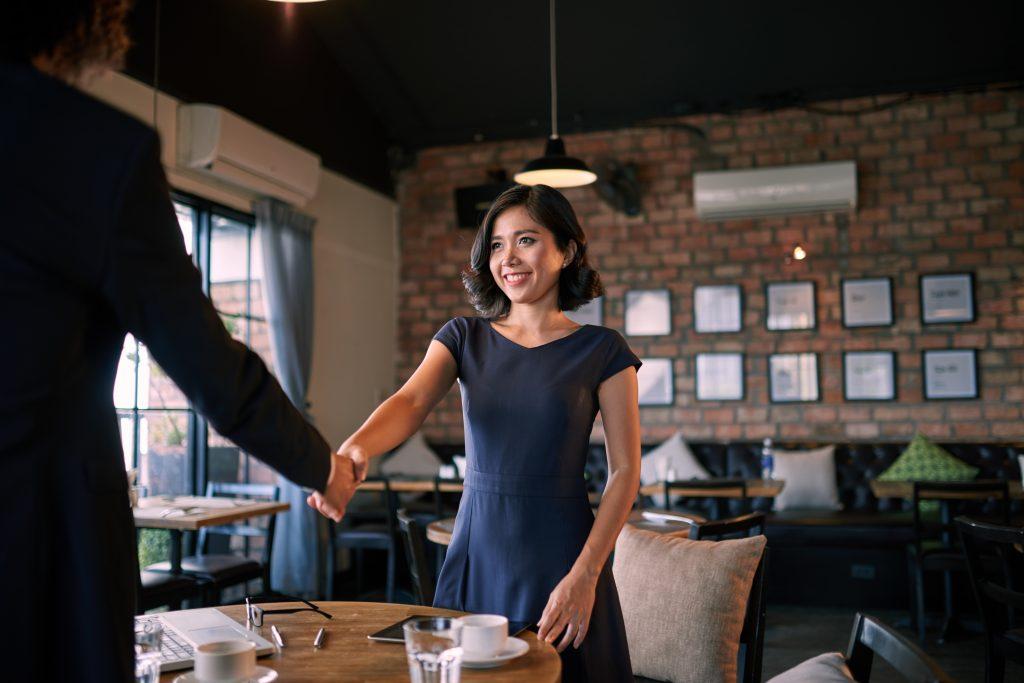 Junge Frau begrüßt Chef beim Bewerbungslunch