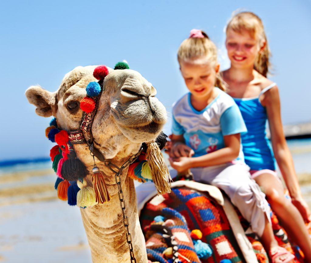 zwei Mädchen auf einem Kamel