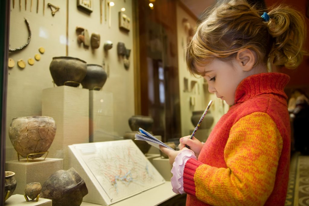 kleines Mädchen im Museum mit Block und Stift