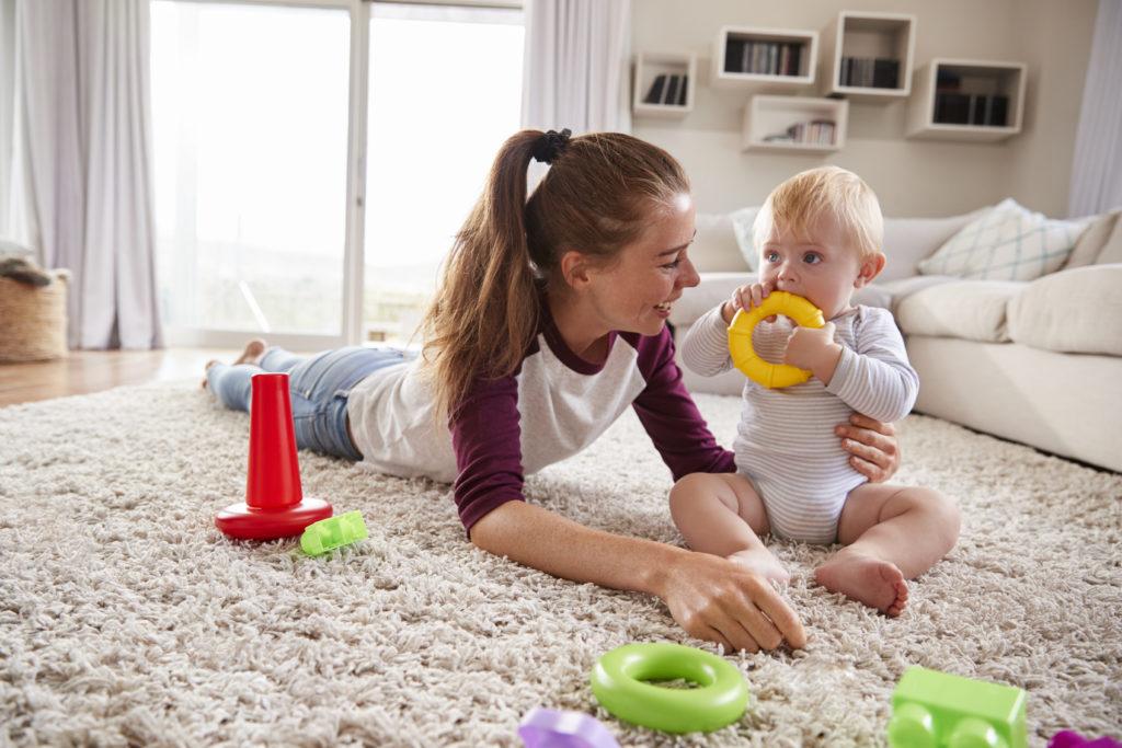 Junge Mutter spielt mit ihrem Baby