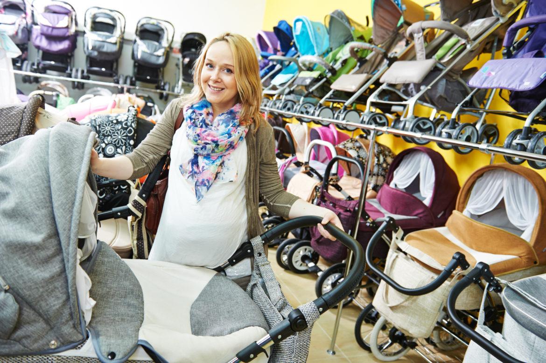 Schwangere junge Frau beim Kinderwagenkauf