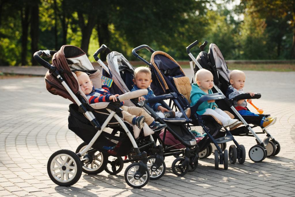 4 verschiedene Kinderwagen nebeneinander mit Baby